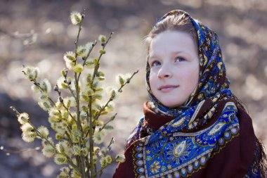 Beautiful Slavic girl with willow twigs in hand