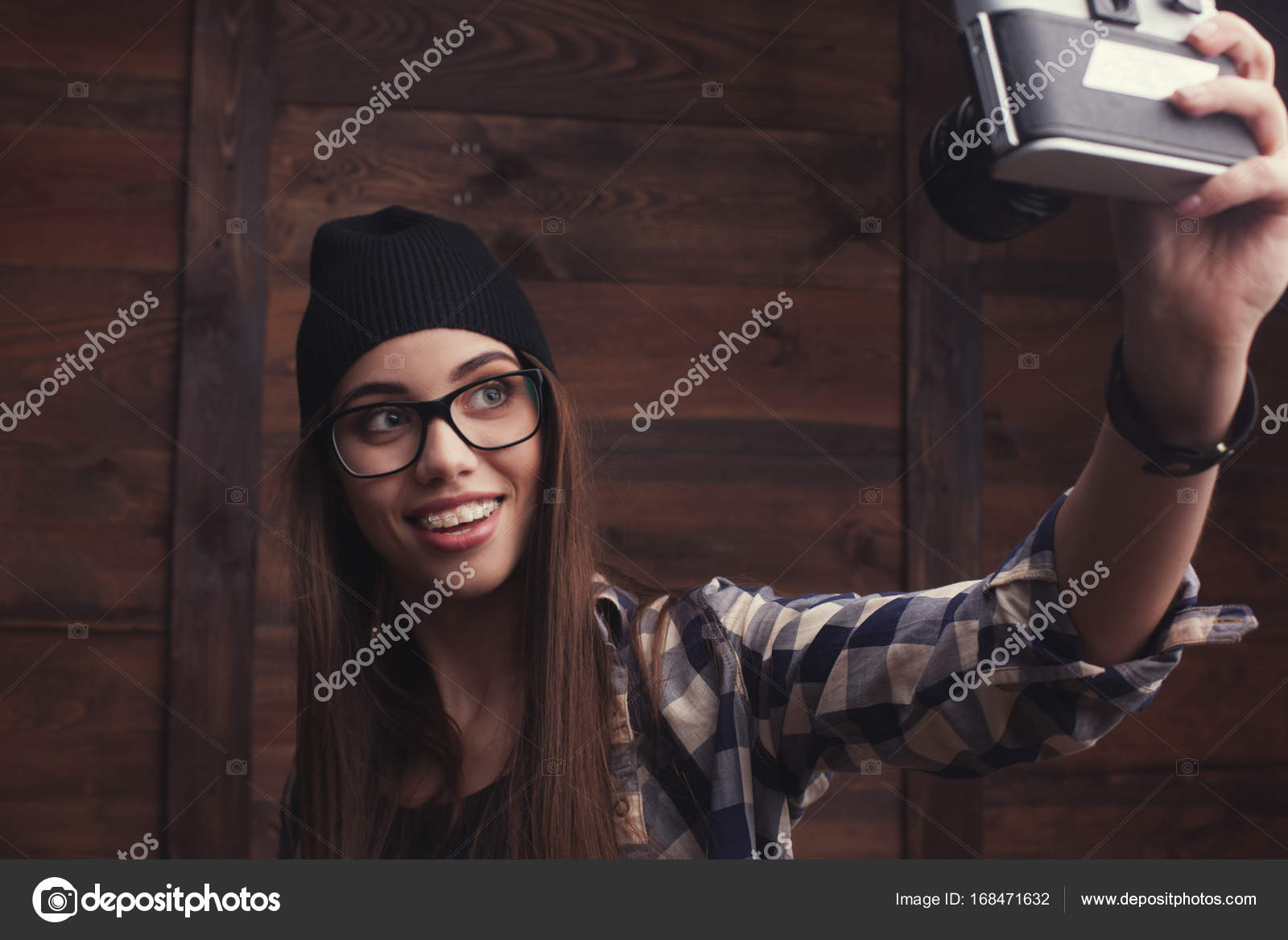 fe822df94bc Hipster girl in glasses and black beanie with vintage camera — Stock Photo