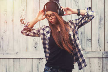 Hipster girl in glasses, headphones and black beanie