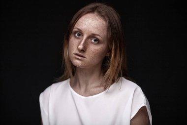 closeup studio portrait of freckled woman without makeup