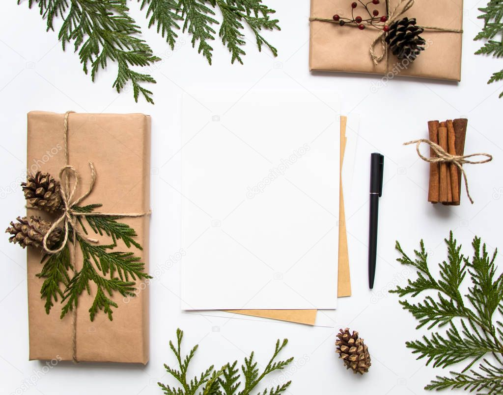 Gift boxes in craft paper and a letter on white background. Christmas or other holiday concept, top view, flat lay