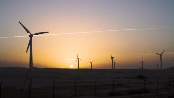 4 k krásný větrný mlýn turbíny využití čisté, zelené, větrné energie siluetu v západu slunce na obloze se sluneční paprsky. Zelená energie