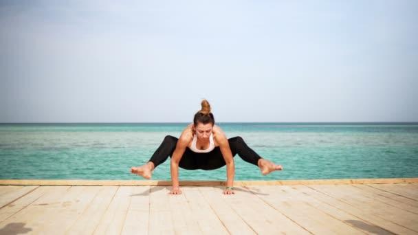 das Mädchen macht Yoga-Pose am Strand der Insel. Statisch. Meer oder Meer glückliche Frau Entspannung. Wasser und Wolken. Hände und blauer Himmel.