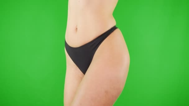 Closeup sexy ženy v kalhotkách ukazují na zeleném pozadí