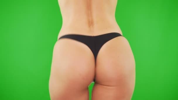 Closeup sexy ženách za kalhotky na zeleném pozadí