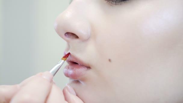 Zblízka atraktivní krásy dívka dělá full make-up. Žena použití červené rty
