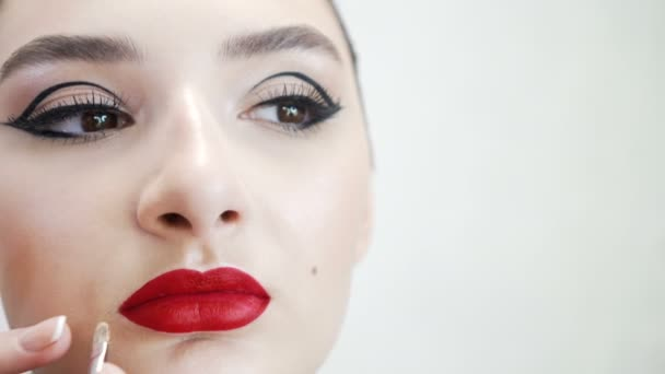 Close up of an attractive beauty girl doing full make-up. Woman applying red lip