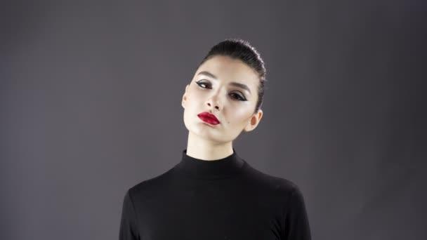 Porträt einer schönen sexy Mädchen. Model posiert auf dunklem Hintergrund für ein Fotoshooting im Studio. ausdrucksstarkes und stilvolles Make-up und Frisur. Nahaufnahme. rote Lippen