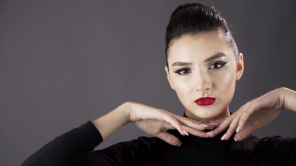 Porträt einer schönen sexy Mädchen. Model posiert auf dunklem Hintergrund für ein Fotoshooting im Studio. Slow mo. Nahaufnahme. rote Lippen