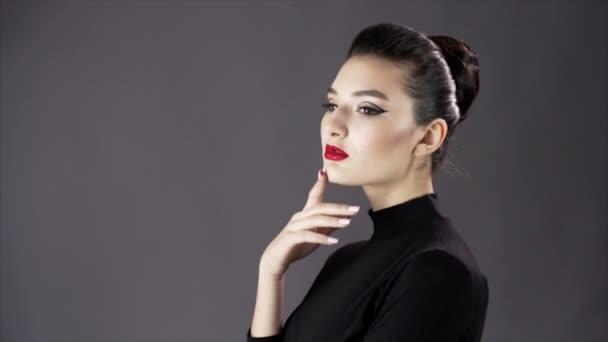 Portrét krásné sexy dívky. Modelka pózuje na tmavém pozadí pro studio focení. Pomalé mo zblízka. Červené rty