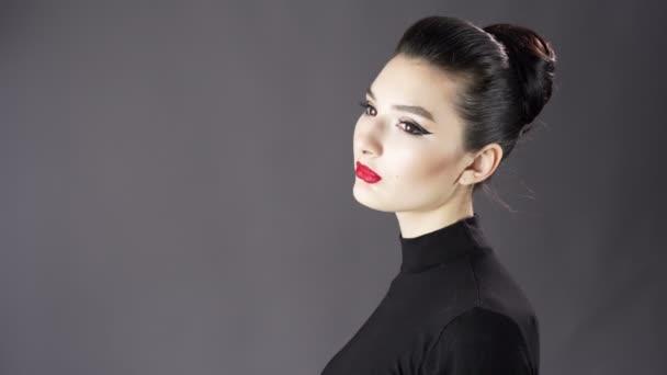 Portrét krásné sexy dívky. Modelka pózuje na tmavém pozadí pro studio focení. Výrazné a stylové líčení a účes. Zblízka. Červené rty