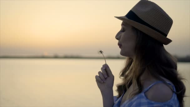 Attractive woman in hat and dress is sitting and looking at sunset