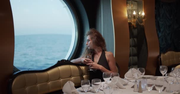 Barcelona, Spain - October 20, 2019: Beatiful woman is sitting alone at table in restaurant on cruise ship, drinking champagne..