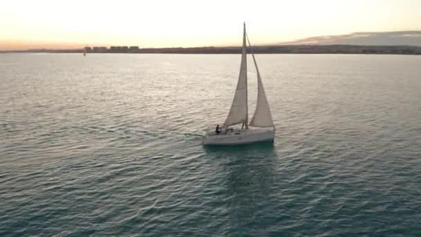 Légi felvétel. Vitorlás jacht a tengeren naplementekor.