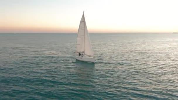 Letecký pohled. Jachta pluje po moři při západu slunce. Dron létá kolem jachty s plachtami.