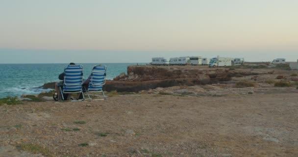 Camping RV. Pár sledování západu slunce vedle kempování rv na venkovní dobrodružství.