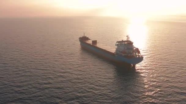 Letecký pohled. Krásný západ slunce nad mořem. Obrovská nákladní loď plovoucí v moři.