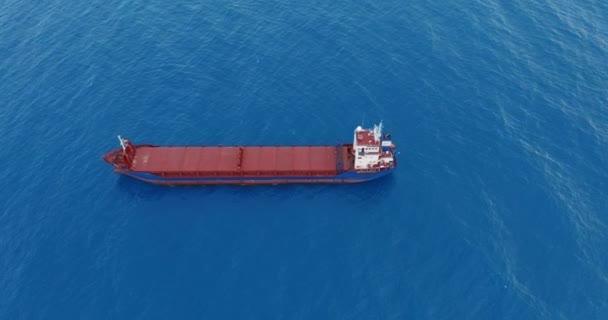 Letecký pohled. Červená paluba nákladní loď plachtění na otevřeném moři.