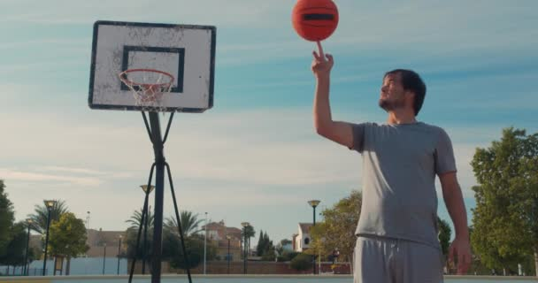 Kosárlabda kiegyensúlyozó és forgó egy ujj játékos egy szabadtéri kosárlabda pályán.