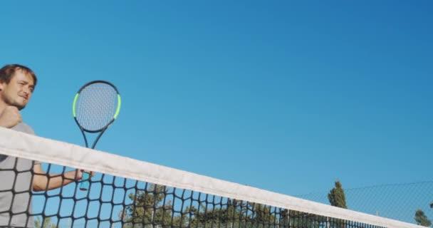 Muž sportovec hraje tenis na venkovním hřišti. Šťastný muž na oslavu úspěchu a vítězství.