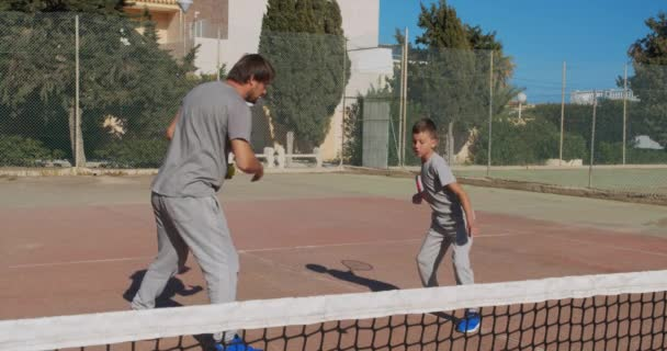 Father and son playing tennis on court. Tennis training.