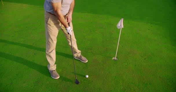 Fešák starší golfista houpání a bít golfový míček na krásném hřišti při západu slunce.
