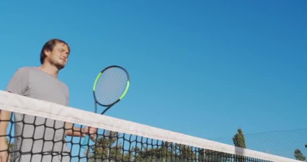 Hráči potřesení rukou po tenis zápas na modrém pozadí oblohy.