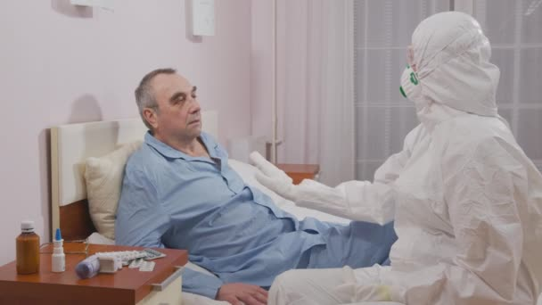 Temperature measurement of a sick elderly man during an epidemic. Infection prevention and control of epidemic. Protective suit and mask.