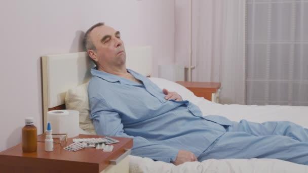 Kranker alter Mann hustet im Bett.