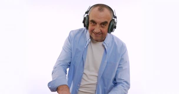 Der alte Mann mit Kopfhörer, Musik hörend, tanzend, lächelnd, fröhlich. Ein sehr flippiger älterer Opa dj.