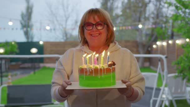 Joyful woman holding a cake with burning candles.
