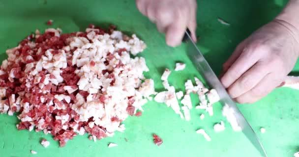 řezník řeže syrové maso s nožem