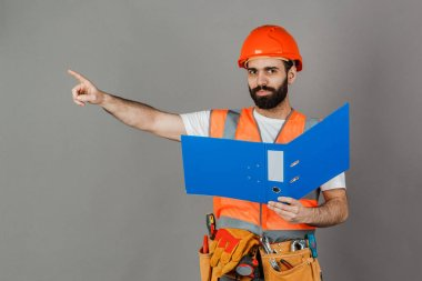 Builder or worker in a protective helmet with drawings in his ha