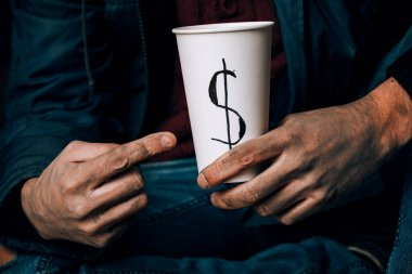 A man begs. He is holding a white paper Cup. The concept of homelessness and poverty