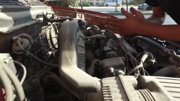 A férfi megjavítja a kocsit..