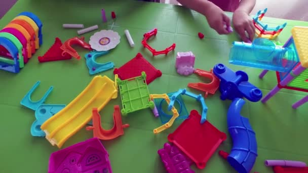 Children play at the table with a building kit