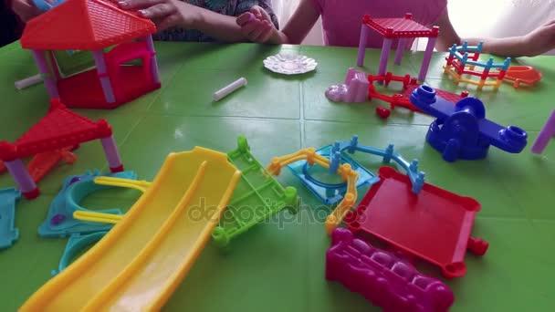 Děti postavit dům z budovy kit. Děti u stolu se hrají