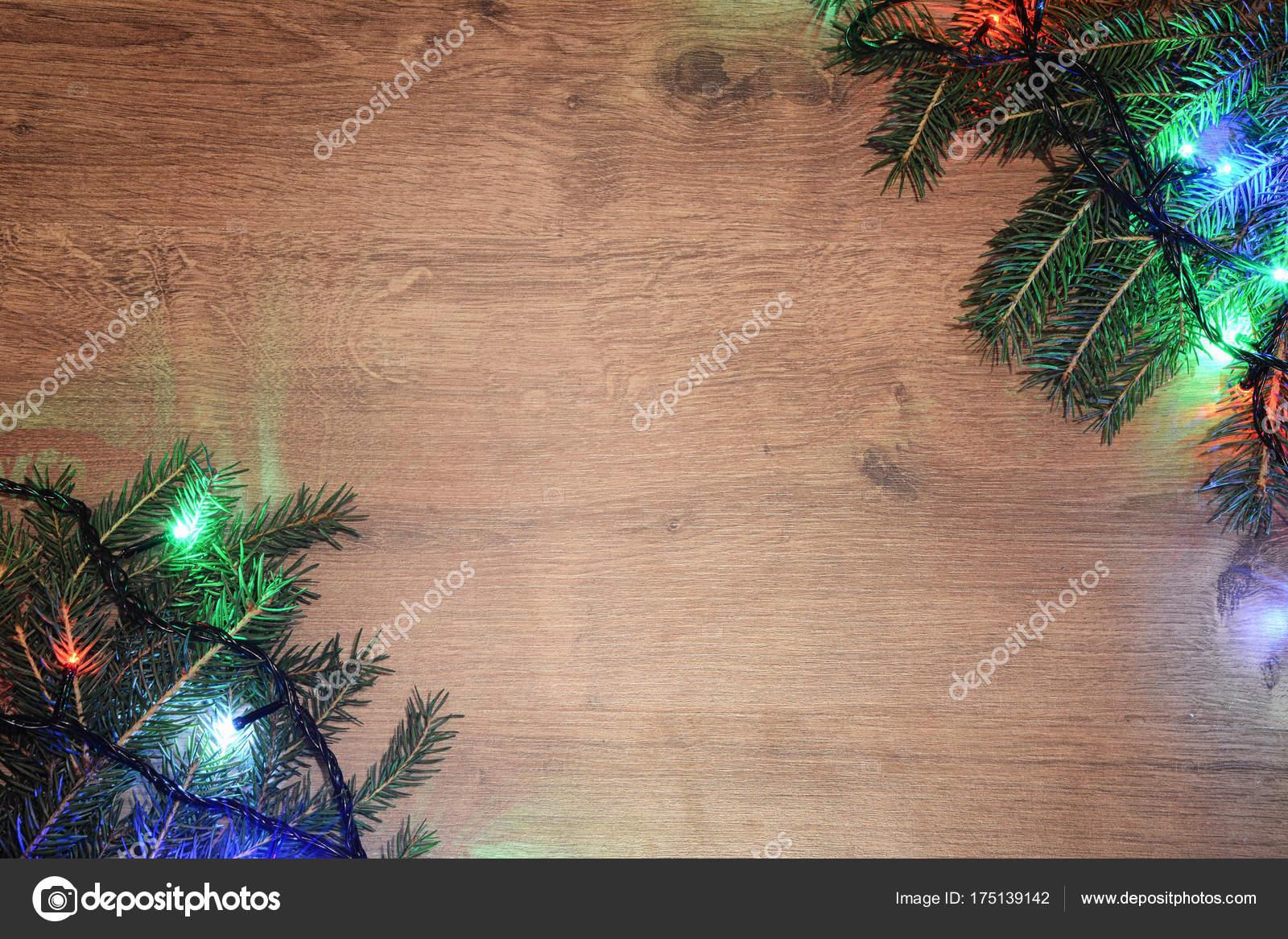 591a764447f Año nuevo eléctrico garland sobre un fondo de madera. Focos brillantes en  una mesa de madera y ramitas de un árbol de Navidad — Foto de  blackroomstudio
