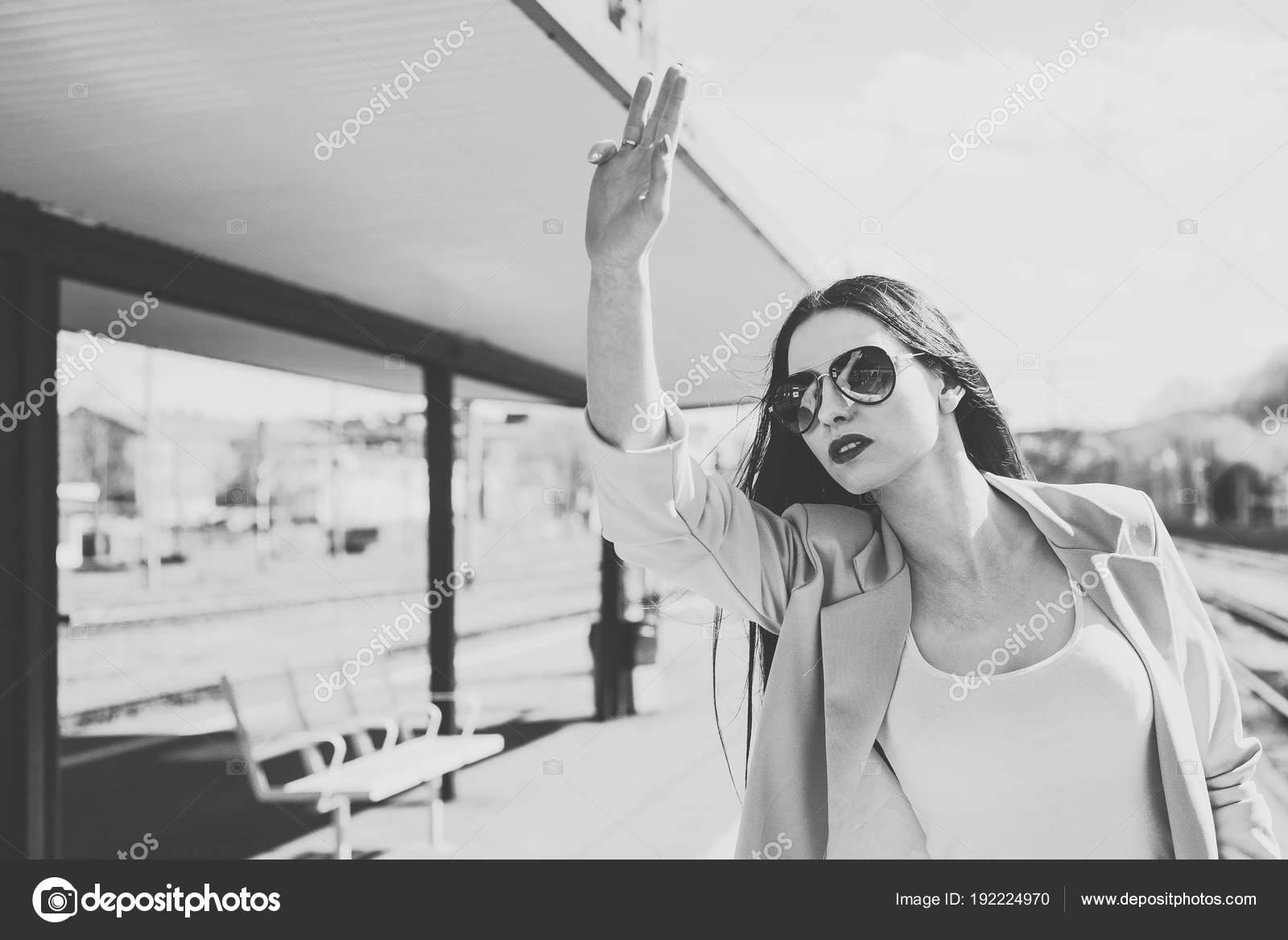 453a39551d Η γυναίκα στην πλατφόρμα θέτει το χέρι καλώντας κάποιον. Μια όμορφη και  ελκυστική γυναίκα φοράει γυαλιά ηλίου. Ταξίδια έννοια