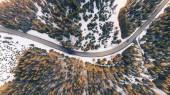 Letecký pohled na vozy na klikaté cestě v horách v zimním lese