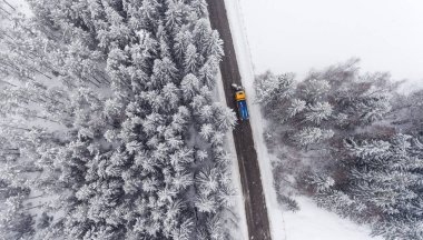 Aerial view of Snowplow truck maintaining road in winter forest.