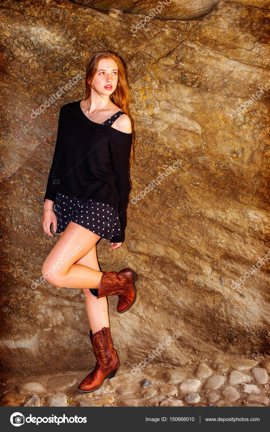 f7e8ce3261d American teenage girl wearing black knit sweater, off one shoulder,  patterned skirt, brown boots, standing against rock wall at Central Park,  New York, ...
