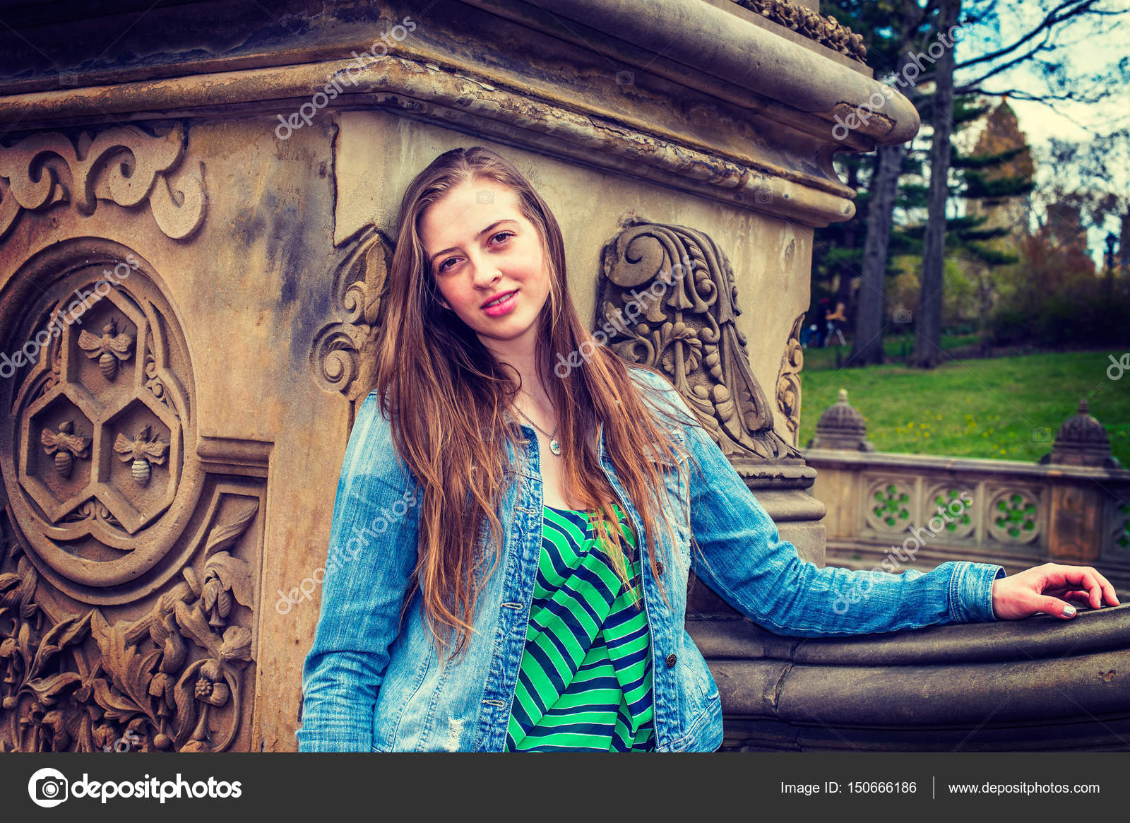 3037f70b7e1 American teenage girl wearing patterned undershirt, Denim jacket, leaning  against column of old fashion style fence, smiling, looking at you.