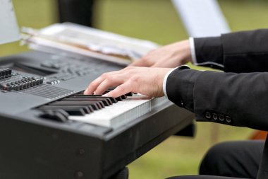 Wedding picnic.  Male hands playing electric piano.