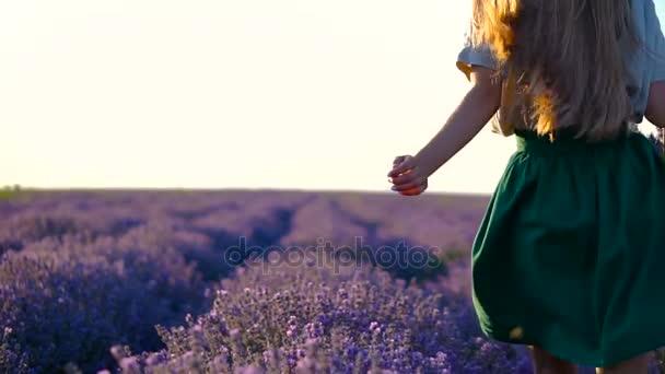 Šťastná Mladá krásná žena běží prostřednictvím levandule pole v bílou košili a zelené šaty