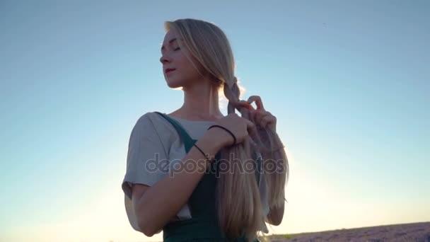 Šťastná Mladá krásná žena splétá copánek vlasy v levandule v bílé a zelené šaty