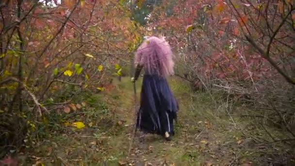 Mladí růžové vlasy čarodějnice v klobouku mě sleduje v mystické podzimním lese. Halloween se blíží.