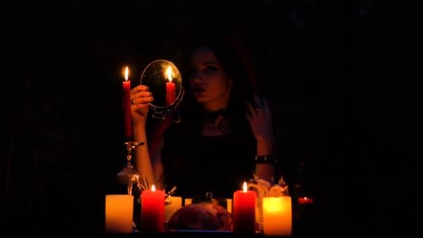 Atraktivní nádherná bruneta čarodějnice se zrcadlem v červený plášť, který vyvolává v mystické podzimním lese. čarodějnictví se srdcem, kuřecí stehna a Dikobraz jehly
