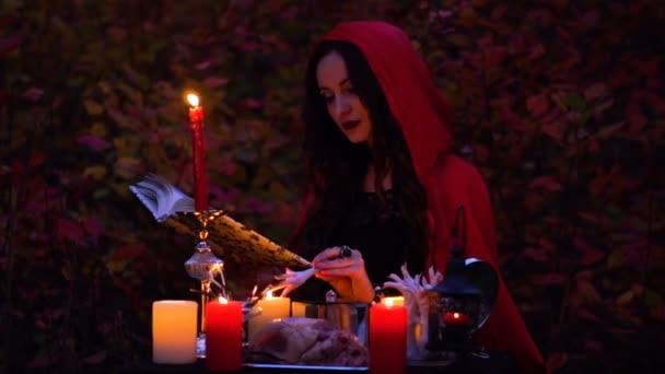 Atraktivní nádherná bruneta čarodějnice v červený plášť, který vyvolává v mystické podzimním lese. čarodějnictví se srdcem, kuřecí stehna a Dikobraz jehly