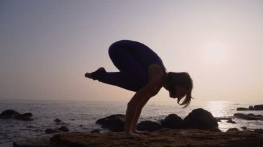 Young woman in bodysuit practicing yoga on the beach above sea at amazing sunrise. Fitness, sport, yoga and healthy lifestyle concept. Girl doing handstand